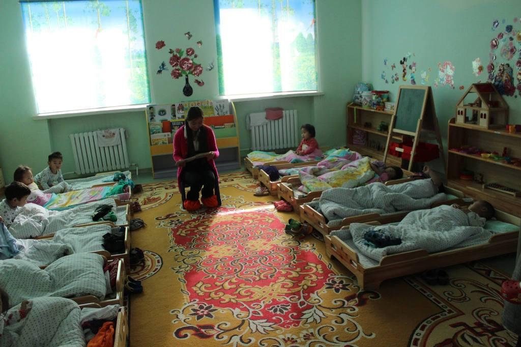 Local university student volunteer reads to kindergarten students before naptime in Mongolia.
