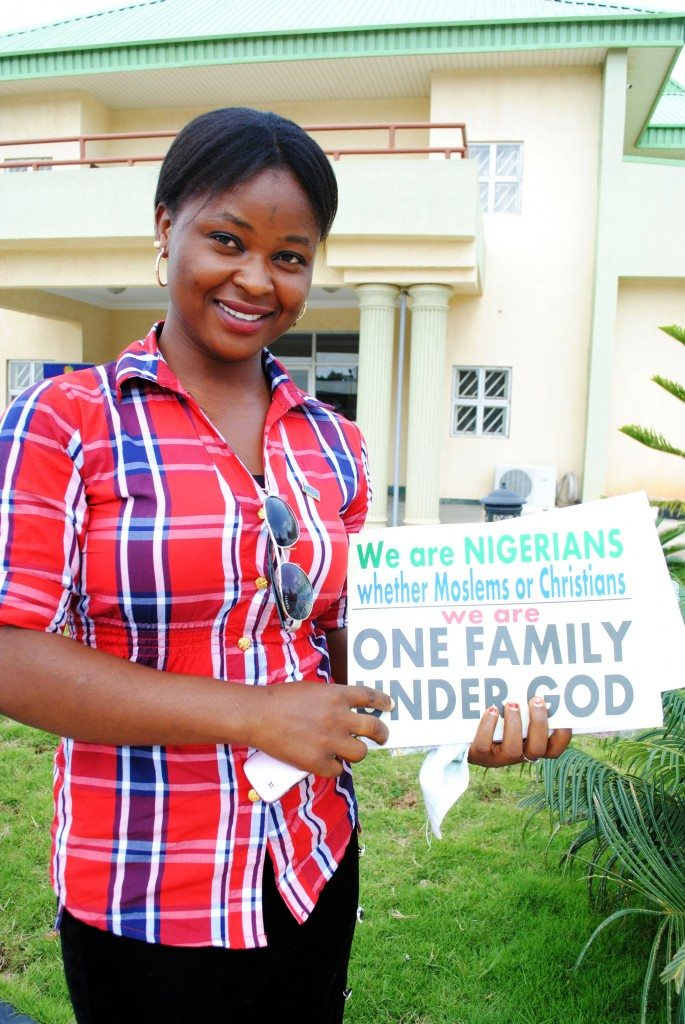 Participant holding a One Family under God sign