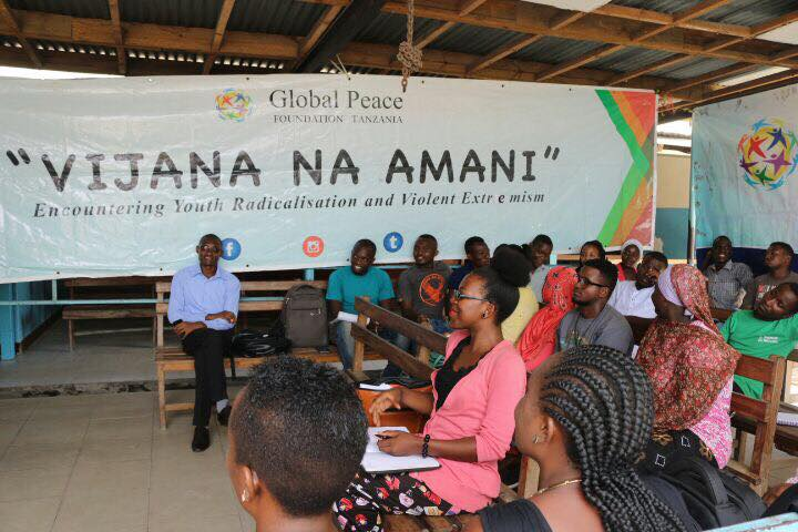 Young leaders sit by banner 'Youth for Peace' in Tanzania workshop