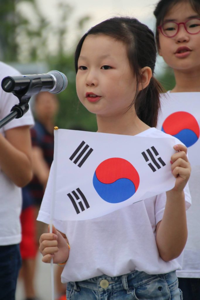 """Young girl in children's choir sings """"Arirang"""" ,holding up the taegeukki, symbolism for both North and South Korea."""